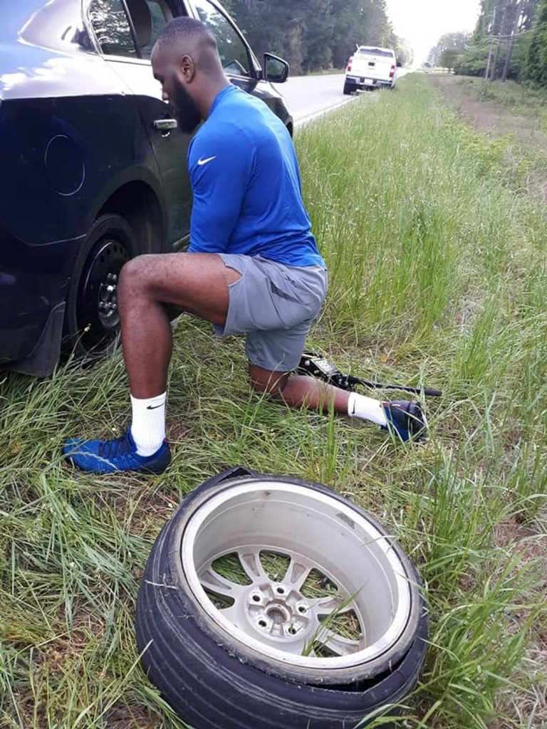 NFL Player changing the tire for his teacher